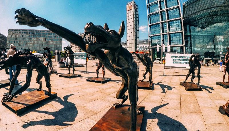 Se você chegasse em Berlim de trem, no início de Agosto, vicie seria recepcionada por uma alcatéia de lobos. Estátuas de bronze e ferro, algumas com dois metros de altura, estariam ali na frente da Hauptbahnhof esperando você chegar. Alguns deles estariam armados, outros estariam fazendo a saudação Nazistas. Uma placa estaria dizendo que os Lobos estão de volta a Berlim mas o que que é isso tudo?